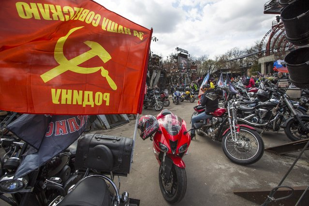 "Members of the Night Wolves biker  group gather to see off Russian bikers leaving for Germany to mark the 70th anniversary of Soviet victory over Nazi Germany, in Moscow, Saturday, April 25, 2015. Message on flag reads ""For our Soviet Motherland"". (Photo by Alexander Zemlianichenko/AP Photo)"