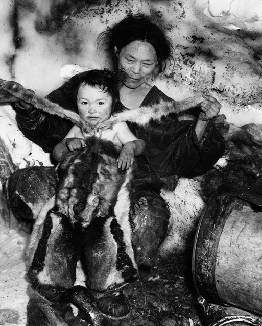 An Inuit mother dresses her young child in a fur snowsuit. (Photo by Hulton-Deutsch Collection/Corbis via Getty Images)