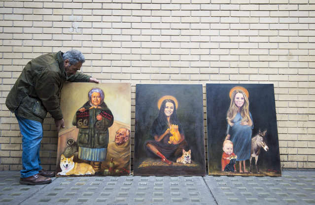 London artist Kaya Mar (L) arranges his paintings depicting members of the royal family, as royal fans continue to wait outside the Lindo Wing at St.Mary's Hospital in north London, Britain, 01 May 2015. Britain's Catherine, The Duchess of Cambridge and Prince William plan to have the birth of their second child at the Lindo Wing, it was confirmed on 09 April. The royal couple are expecting their second child. (Photo by Facundo Arrizabalaga/EPA)