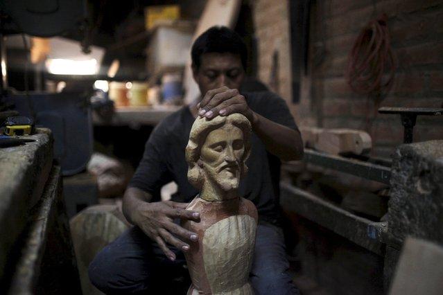 An assistant of Manuel de Jesus Quilizapa adjusts the head of a statue of El Jesus Nazareno in his workshop in Izalco, El Salvador March 11, 2016. (Photo by Jose Cabezas/Reuters)