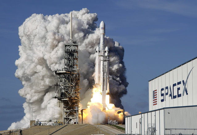 A Falcon 9 SpaceX heavy rocket lifts off from pad 39A at the Kennedy Space Center in Cape Canaveral, Fla., Tuesday, February 6, 2018. The Falcon Heavy, has three first-stage boosters, strapped together with 27 engines in all. (Photo by John Raoux/AP Photo)