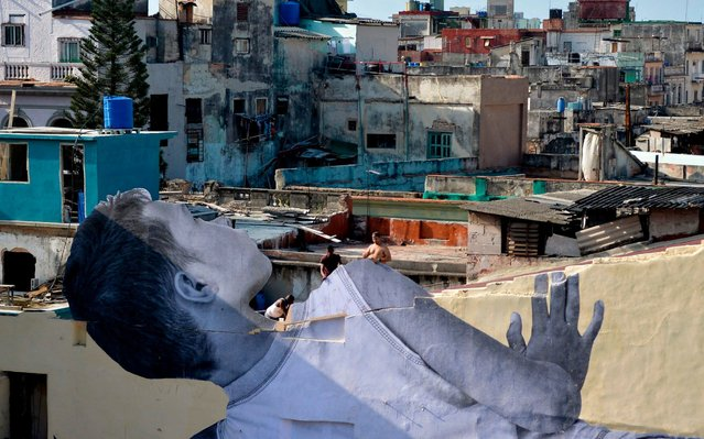 """People work on the finishing touches of the work """"Giants, peeking at the city"""", a huge collage of a picture of a Cuban boy by French artist and photographer Jean Rene, aka JR, as part of the 13th Havana Biennial, on April 10, 2019. JR has exhibited his huge collages in the favelas of Rio de Janeiro and around the Louvre pyramid in Paris, among other sites. (Photo by Yamil Lage/AFP Photo)"""