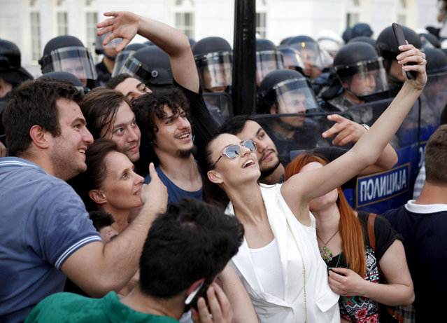 Protestors take a selfie in front of a police cordon during a demonstration in front of the Government building in Skopje Macedonia, on Tuesday, May 5, 2015. (Photo by Boris Grdanoski/AP Photo)