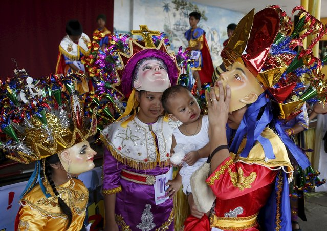 """A woman, and her daughters, dressed as penitents locally called """"Morions"""", carries her baby during the start of Holy Week celebrations in Mogpog, Marinduque in central Philippines March 21, 2016. (Photo by Erik De Castro/Reuters)"""