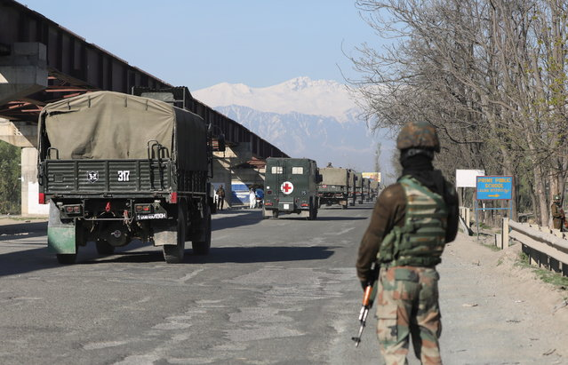 Indian army and paramilitary soldiers stand guard as an Indian Army convoy crosses the national highway on the outskirts of Srinagar, the summer capital of Indian Kashmir, 07 April 2019. The Jammu and Kashmir government has banned civilian traffic on Srinagar-Jammu national highway for two days in a week (Sunday and Wednesday) for safe passage of Indian security forces convoys. The authorities have deployed civil magistrates on the highway to facilitate travel of medical emergencies, students and tourists on highway by giving them on-spot travel passes. Earlier, after February 14 suicide car bombing on CRPF convoy in which 40 paramilitary personnel were killed, forces were stopping civilian vehicles during convoy movements. (Photo by Farooq Khan/EPA/EFE)