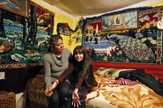Niculina Fieraru, 39, poses with her daughter Flori Gabriela Dumitrache, 13, in their room in Gura Sutii village, Romania February 25, 2014. Niculina Fieraru is unemployed and has two children. She hopes that her daughter Flori Gabriela will become a seamstress. Flori Gabriela wants to become a pop singer and she hopes to go to high school in a town 23 km (14 miles) away, but her family cannot afford to pay for it. (Photo by Bogdan Cristel/Reuters)