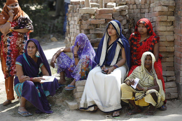 Indian women wait to cast their votes in the seventh and final phase of national elections, on the outskirts of Varanasi, India, Sunday, May 19, 2019. Indians are voting in the seventh and final phase of national elections, wrapping up a 6-week-long long, grueling campaign season with Prime Minister Narendra Modi's Hindu nationalist party seeking reelection for another five years. Counting of votes is scheduled for May 23. (Photo by Rajesh Kumar Singh/AP Photo)