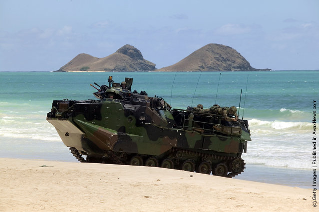 A U.S. military Amphibious Assault Vehicle (AAV) from the USS Rushmore rolls up on the beach