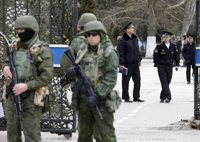 Armed men (L), believed to be Russian servicemen, stand guard outside Ukraine's naval headquarters after it was taken over by pro-Russian forces, as Russian naval officers (R) are seen in the background, in Sevastopol, March 19, 2014. (Photo by Vasily Fedosenko/Reuters)
