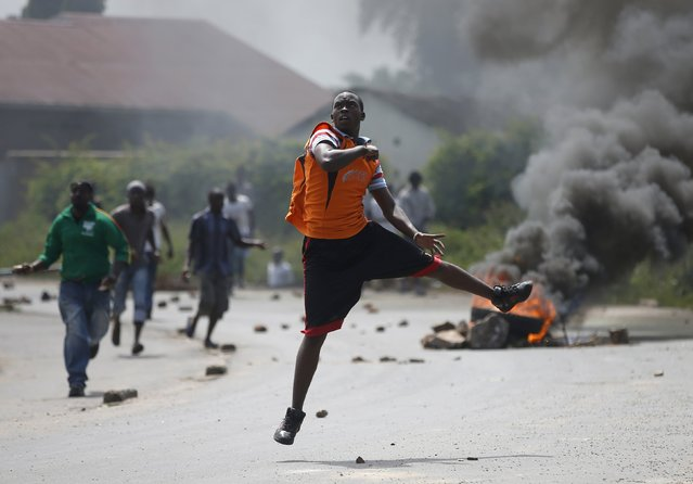 Protesters run to throw stones at policemen near a burning barricade during a protest against Burundi President Pierre Nkurunziza and his bid for a third term in Bujumbura, Burundi, May 21, 2015. (Photo by Goran Tomasevic/Reuters)