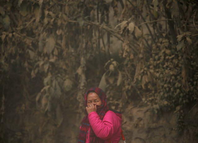 A woman covers her face as she stands along a dusty road in Kathmandu, Nepal February 27, 2017. (Photo by Navesh Chitrakar/Reuters)