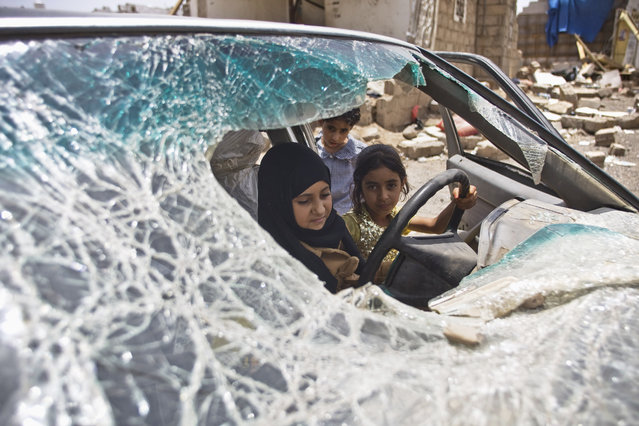 Yemeni girls play with a vehicle damaged by Saudi-led coalition airstrikes in Sanaa, Yemen, Monday, May 18, 2015. (Photo by Hani Mohammed/AP Photo)