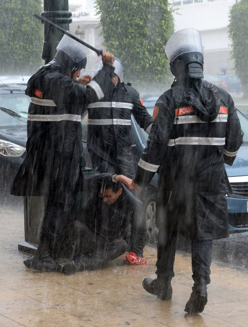 Riot police assault a demonstrator during a protest against unemployment in front of the Moroccan Parliament in Rabat on April 2, 2014. (Photo by Fadel Senna/AFP Photo)