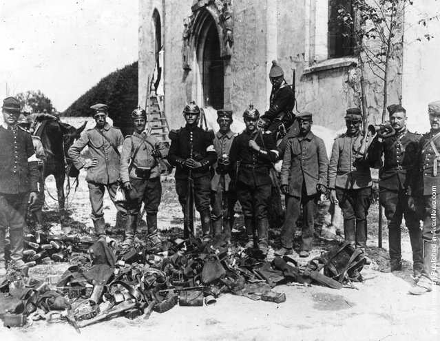 French soldiers wearing German helmets stand with equipment captured from the enemy troops after the Battle of the Marne in WWI
