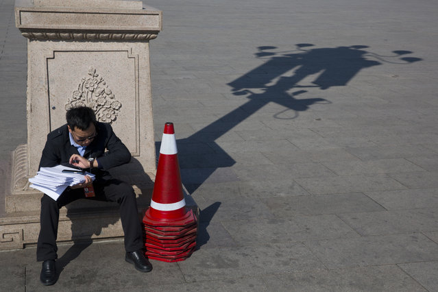 In this photo taken Wednesday, March 8, 2017, a staff member checks his watch as he waits near the Great Hall of the People where a plenary session of the National People's Congress is held in Beijing, China. (Photo by Ng Han Guan/AP Photo)