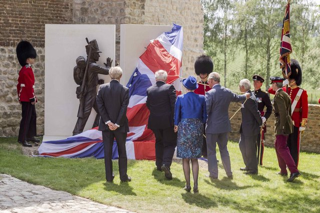 Britain's Prince Charles (4thL) holds a rope as he unveils a monument during a ceremony for the opening of the Hougoumont farm as part of the bicentennial celebrations for the Battle of Waterloo, near Waterloo, Belgium June 17, 2015. The commemorations for the 200th anniversary of the Battle of Waterloo will take place in Belgium on June 19 and 20. REUTERS/Geert Vanden Wijngaert/Pool