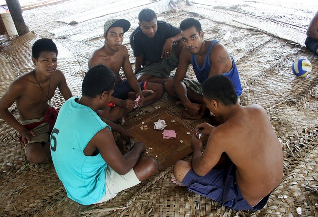 Prisoners play cards under a shelter located in a prison on Kiritimati Island, part of the Pacific Island nation of Kiribati, April 5, 2016. (Photo by Lincoln Feast/Reuters)
