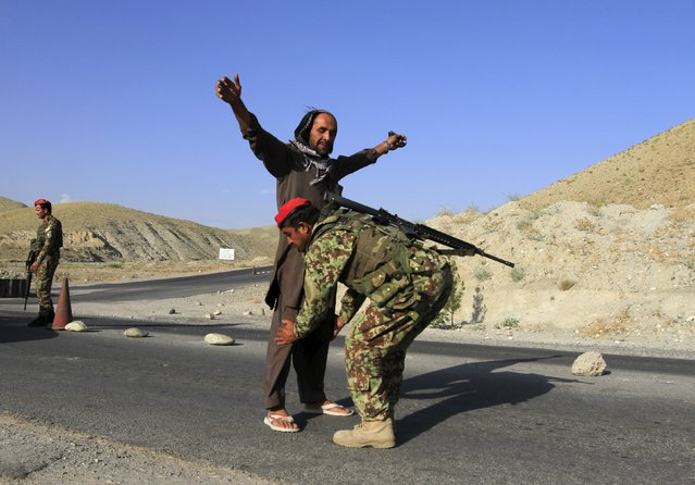 An Afghan National Army soldier (ANA) inspects passengers at a checkpoint on the outskirts of Jalalabad province June 29, 2015. Fighters loyal to Islamic State have seized substantial territory in Afghanistan for the first time, witnesses and officials said, wresting areas in the east from rival Taliban insurgents in a new threat to stability. (Photo by Reuters/Parwiz)