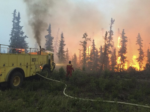 Firefighters tackle a wildfire near the town of La Ronge, Saskatchewan July 4, 2015 in a picture provided by the Saskatchewan Ministry of Government Relations. The Western Canadian province of Saskatchewan said on Sunday it was evacuating an additional 8,000 people from the far north of the province, as wildfires continue to spread and threaten homes. The provincial government said that as of Saturday there were 114 active fires in the province. More than 5,000 residents have already been moved out of the area in the past week. (Photo by Reuters/Saskatchewan Ministry of Government Relations)
