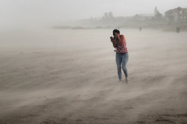 A woman seeks cover from wind, blowing sand and rain whipped up by Hurricane Dorian as she walks on the beach on September 2, 2019 in Cocoa Beach, Florida. Dorian, once expected to make landfall near Cocoa Beach as a category 4 storm, is currently predicted to turn north and stay off the Florida coast, lessening the impact on the area. (Photo by Scott Olson/Getty Images)