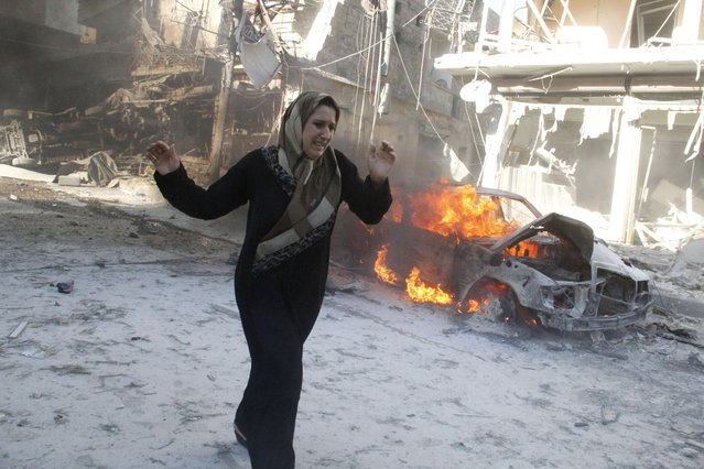 A Syrian woman walks past the burning wreckage of a car following reported air strikes by government forces on May 1, 2014 in the Halak neighbourhood in northeastern Aleppo. According to the Syrian Observatory for Human Rights, at least 33 civilians were killed in the attack. (Photo by Khaled Khatib/AFP Photo/AMC)
