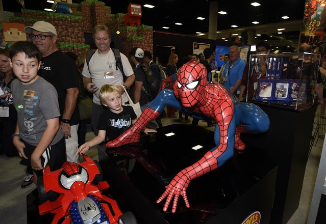 Fans walk past a Spiderman display on Preview Night at the 2015 Comic-Con International held at the San Diego Convention Center Wednesday, July 8, 2015, in San Diego. (Photo by Denis Poroy/Invision/AP Photo)