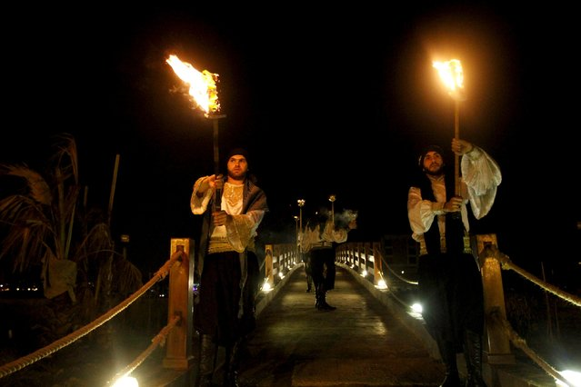 Muslim men wearing traditional clothes, hold torches as they take part in a religious festivity during the holy month of Ramadan on a tiny island in Tripoli, northern Lebanon July 11, 2015. (Photo by Omar Ibrahim/Reuters)