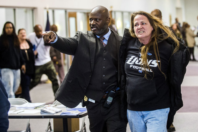 In this Thursday, April 20, 2017, photo, Flint police Officer Kristopher Jones removes resident Leah Palladeno, in handcuffs, from a town hall meeting at House of Prayer Missionary Baptist Church, related to the city's crisis with lead-tainted water, in Flint, Mich. Police say six people were arrested for disorderly conduct or other reasons. The event was held after Flint Mayor Karen Weaver reversed course Tuesday and recommended that Flint continue getting its drinking water from a Detroit-area system long term instead of a new pipeline. (Photo by Jake May/The Flint Journal-MLive.com via AP Photo)