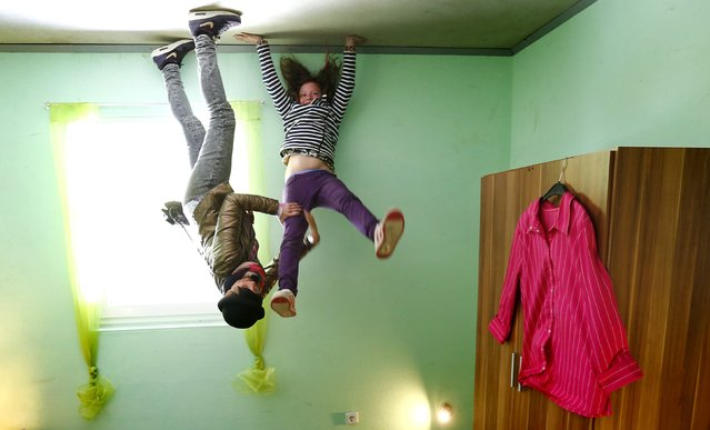 """Dutch tourists Rosanna (L) and Nova pose for a photograph inside the bedroom of the """"Crazy House"""", which is completely built upside-down, in the village of Affoldern near the Edersee lake, May 7, 2014. Three friends came up with the idea to build the tourist attraction, which cost about 200,000 euros and took some six weeks to complete.  Camera was turned 180 degrees for the picture. (Photo by Kai Pfaffenbach/Reuters)"""