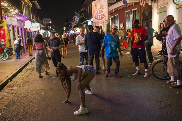 A woman twerks to music from a nearby club along Bourbon Street, located in the French Quarter of New Orleans, Louisiana, July 11, 2015. (Photo by Adrees Latif/Reuters)