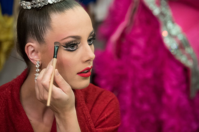 """Dancer Claudine Van Den Bergh, 27, puts on her make-up before entering the stage in the review """"Feerie"""" at the Moulin Rouge in Paris, France, June 12, 2018. Van Den Bergh has been dancing at the Moulin Rouge for seven years and has been Principal for three years. """"At the moment I rush out to the backstage, I know exactly where to go, what to do, where my next costume is for the next part"""" she said. (Photo by Philippe Wojazer/Reuters)"""