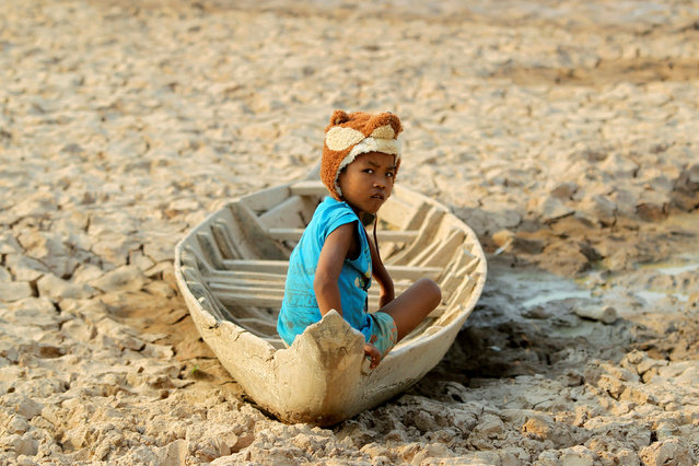 A girl sits on her boat at a Bak Angrout dried up pond at the drought-hit Kandal province in Cambodia May 13, 2016. (Photo by Samrang Pring/Reuters)