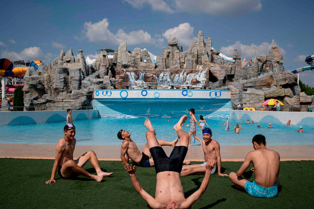 In a photo taken on June 16, 2019 swimmers rest beside a wave pool at the Munsu water park in Pyongyang. (Photo by Ed Jones/AFP Photo)