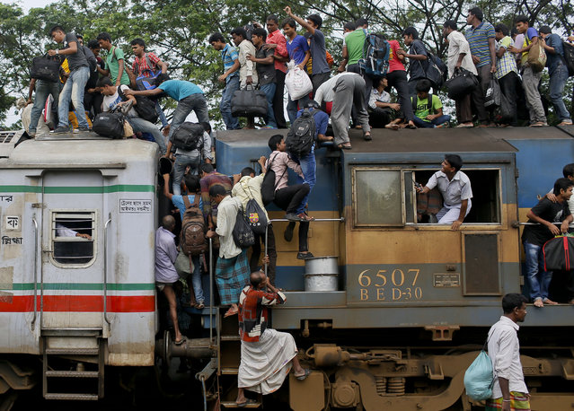 Bangladeshi Muslims try to climb on to the roof of an overcrowded train as they head to their homes ahead of Eid al-Fitr at a railway station in Dhaka, Bangladesh, Thursday, July 16, 2015. Hundreds of thousands of people working in Dhaka plan to leave for their home towns to celebrate with their family the upcoming Eid al-Fitr. (Photo by A. M. Ahad/AP Photo)