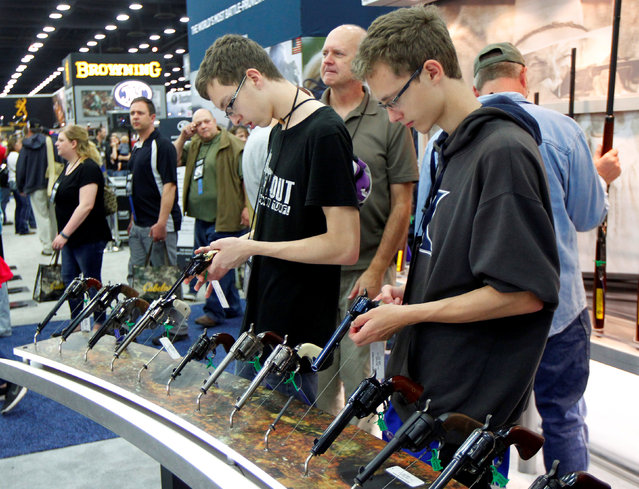 Gun enthusiasts look over Benelli USA guns at the National Rifle Association's annual meetings & exhibits show in Louisville, Kentucky, May 21, 2016. (Photo by John Sommers II/Reuters)