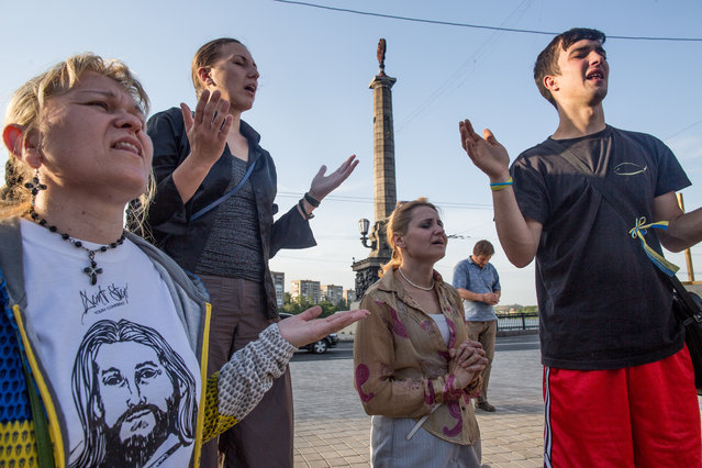 An interdenominational Christian group pray for Ukraine at the Kalmius embankmentt near Constitution square, May 23, 2014 in Donetsk. The group is on the 77th day of prayer for Ukraine and have been attacked and intimidated frequently. Ukrainian security forces have been tightening the ring around Donetsk, and the number of clashes has increased in recent days. (Photo by Evelyn Hockstein/The Washington Post)