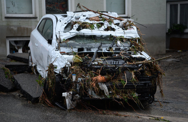 A destroyed car sits in a street in Braunsbach, southwestern Germany, Monday, May 30, 2016. (Photo by Franziska Kraufmann/DPA via AP Photo)