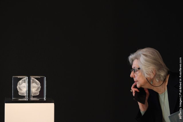 A visitor looks at an artwork entitled 'My Soul' by Katharine Dowson which consists of a laser etched lead chrystal glass formation in the shape of a brain, and was created using the artists own MRI Scan