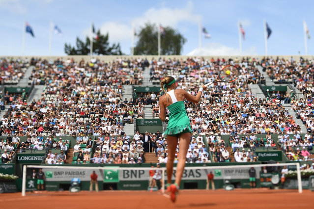 A photo taken with a tilt and shift lens shows France' s Kristina Mladenovic returning the ball to Spain' s Garbine Muguruza during their tennis match at the Roland Garros 2017 French Open on June 4, 2017 in Paris. (Photo by Francois Xavier Marit/AFP Photo)