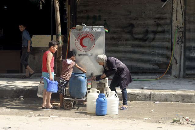 Residents fill containers with water in Aleppo's eastern district of Tariq al-Bab, Syria, August 1, 2015. (Photo by Abdalrhman Ismail/Reuters)