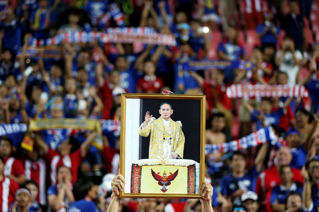 """A soccer player from the Thai national team displays a picture of Thailand's King Bhumibol Adulyadej after winning the """"King's Cup"""" at Rajamangala stadium in Bangkok, Thailand, June 5, 2016. (Photo by Athit Perawongmetha/Reuters)"""