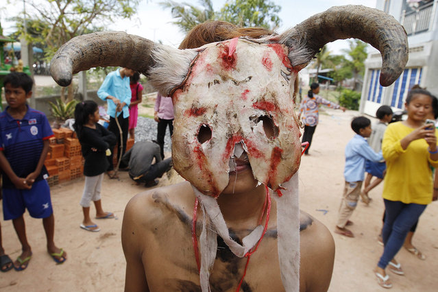 A Cambodian resident wearing a mask attends a ceremony at Pring Ka-Ek village on the outskirts of Phnom Penh, Cambodia, 09 June 2016. Villagers organized a ceremony to continue their local traditions by paying respect to the Neakta Pring Ka-Ek (Spirit house) to prevent them from diseases and to achieve abundant rice harvests and other agricultural yields. (Photo by Mak Remissa/EPA)