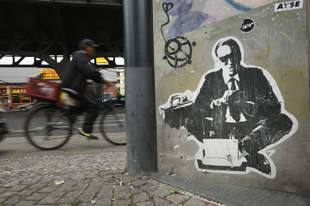 A man on a bicycle rides past stret art in Skalitzer Strasse in Kreuzberg district on June 26, 2014 in Berlin, Germany. Berlin, with its long tradition of counter-culture, has become a mecca for street art of all dimensions and messages. (Photo by Sean Gallup/Getty Images)