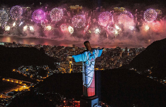 A handout photo made available by Riotour shows a fireworks display behind Christ the Redeemer during New Year's Eve celebrations in Rio de Janeiro, Brazil, 01 January 2020. (Photo by Fernando Maia/EPA/EFE)