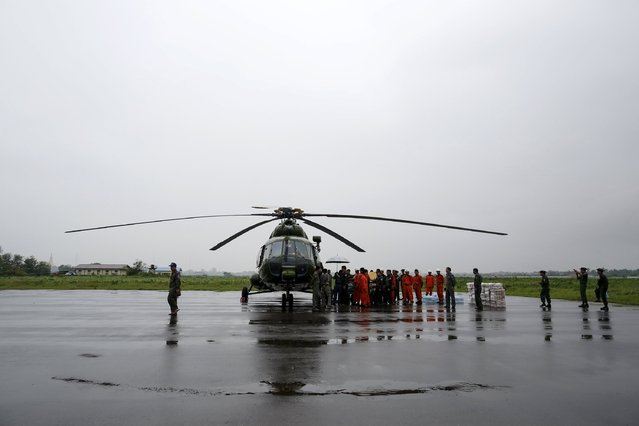 Soldiers and rescue workers load food for storm victims on the military helicopter in Sittwe airport in Rakhine state, Myanmar, August 4, 2015. Myanmar said on Tuesday it had appealed for international assistance to help provide food, temporary shelter and clothing for more than 210,000 people affected by widespread flooding following weeks of heavy monsoon rains. At least 47 people have died in the floods, according to the government. (Photo by Soe Zeya Tun/Reuters)