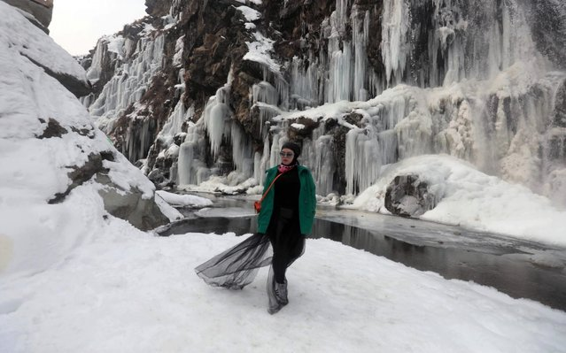 A tourist from Malaysia poses for a photograph near a frozen waterfall in Drang area of Tangmarg, north of Srinagar, the summer capital of Indian Kashmir, 02 January 2020. Kashmir valley is in a grip of intense cold wave conditions resulting in frozen water bodies and water supply lines. (Photo by Farooq Khan/EPA/EFE/Rex Features/Shutterstock)