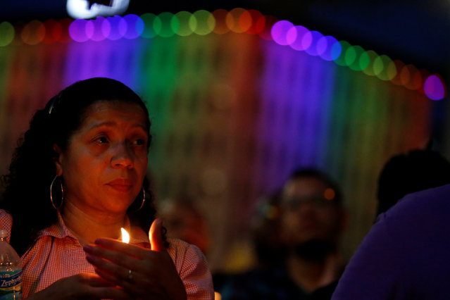 People take part in a candlelight memorial service the day after a mass shooting at the Pulse gay nightclub in Orlando, Florida, U.S. June 13, 2016. (Photo by Carlo Allegri/Reuters)