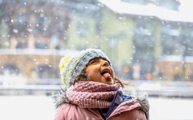 Raya Ramchand, 5, of McKinney, Texas, catches snowflakes on her tongue on a snowy Christmas Day in Vail, Colo., Wednesday, December 25, 2019. The town is bustling with holiday tourists, and activities continue through the New Year. (Photo by Chris Dillmann/Vail Daily via AP Photo)