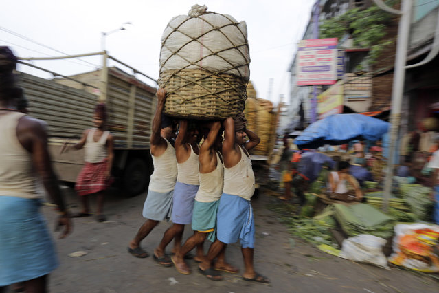 Indian laborers carry a load pf vegetables at a wholesale market in Kolkata, india, Wednesday, July 9, 2014. India's new government presents its inaugural budget this week in the first substantive test of whether Prime Minister Narendra Modi will deliver on ambitious promises to revive stalled economic growth. (Photo by Bikas Das/AP Photo)