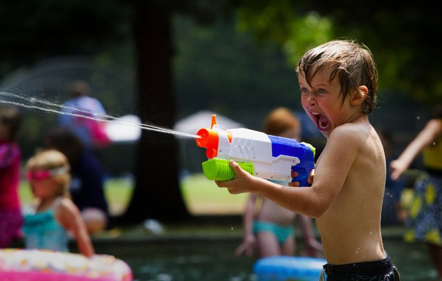 Five-year-old Cian Fitzgerald of West Seattle is full of enthusiasm as he shoots water out of his squirt gun at the Lincoln Park wading pool Tuesday, July 7, 2015. (Photo by Ellen M. Banner/The Seattle Times)
